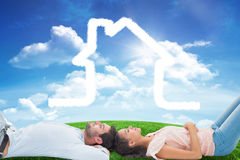Composite image of attractive young couple lying down Stock Photos