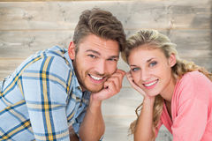 Composite image of attractive young couple lying and smiling at camera. Attractive young couple lying and smiling at camera against bleached wooden planks Stock Photos