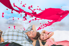 Composite image of attractive young couple lying smiling at camera. Attractive young couple lying smiling at camera against clouds in a room Royalty Free Stock Image