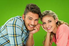 Composite image of attractive young couple lying and smiling at camera. Attractive young couple lying and smiling at camera against green vignette Royalty Free Stock Photo