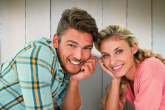 Composite image of attractive young couple lying and smiling at camera. Attractive young couple lying and smiling at camera against wooden planks Royalty Free Stock Photography