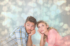 Composite image of attractive young couple lying and thinking Stock Photography