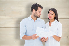 Composite image of attractive young couple reading their bills Stock Photos