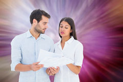 Composite image of attractive young couple reading their bills Royalty Free Stock Photo