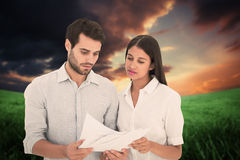 Composite image of attractive young couple reading their bills Royalty Free Stock Photos