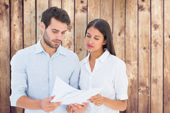Composite image of attractive young couple reading their bills Stock Image