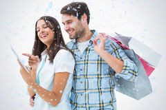 Composite image of attractive young couple with shopping bags and tablet pc Royalty Free Stock Photography