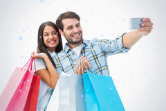 Composite image of attractive young couple with shopping bags taking a selfie Royalty Free Stock Photography
