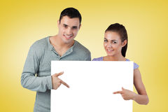 Composite image of attractive young couple showing card Royalty Free Stock Photo