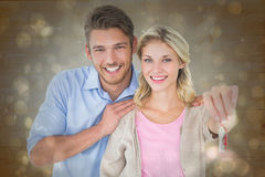 Composite image of attractive young couple showing new house key Royalty Free Stock Image