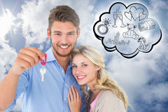 Composite image of attractive young couple showing new house key Stock Photo