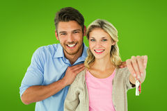 Composite image of attractive young couple showing new house key Stock Photos