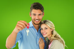Composite image of attractive young couple showing new house key Royalty Free Stock Photo