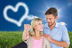 Composite image of attractive young couple showing new house key Royalty Free Stock Photos