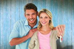 Composite image of attractive young couple showing new house key Stock Image
