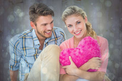 Composite image of attractive young couple sitting holding heart cushion Royalty Free Stock Images