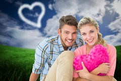 Composite image of attractive young couple sitting holding heart cushion Royalty Free Stock Photography