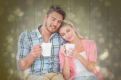 Composite image of attractive young couple sitting holding mugs Royalty Free Stock Image