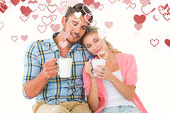 Composite image of attractive young couple sitting holding mugs. Attractive young couple sitting holding mugs against valentines heart design stock photography