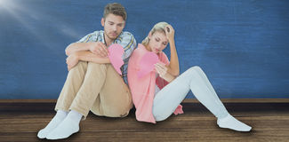 Composite image of attractive young couple sitting holding two halves of broken heart Royalty Free Stock Photos