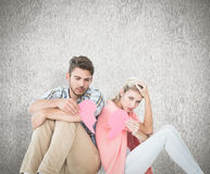 Composite image of attractive young couple sitting holding two halves of broken heart Stock Photos