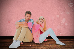 Composite image of attractive young couple sitting holding two halves of broken heart Stock Image