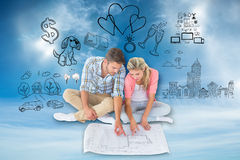 Composite image of attractive young couple sitting looking at blueprint Stock Photos