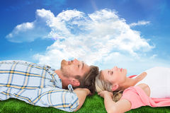Composite image of attractive young couple sleeping peacefully. Attractive young couple sleeping peacefully against cloud heart Stock Photos