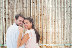 Composite image of attractive young couple smiling at camera Royalty Free Stock Photography