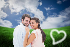 Composite image of attractive young couple smiling at camera Royalty Free Stock Images