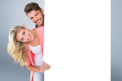 Composite image of attractive young couple smiling at camera Stock Photography