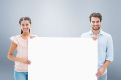 Composite image of attractive young couple smiling at camera holding poster Royalty Free Stock Images