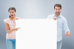 Composite image of attractive young couple smiling at camera holding poster Royalty Free Stock Image
