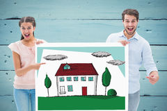Composite image of attractive young couple smiling at camera holding poster Stock Images