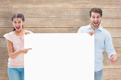 Composite image of attractive young couple smiling at camera holding poster Stock Image