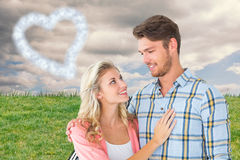 Composite image of attractive young couple smiling at each other Royalty Free Stock Photo