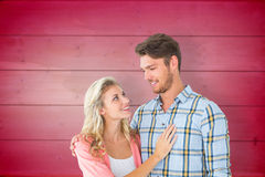 Composite image of attractive young couple smiling at each other Royalty Free Stock Photos
