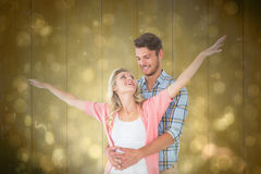 Composite image of attractive young couple smiling and embracing Stock Images