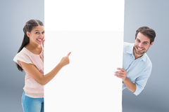 Composite image of attractive young couple smiling and holding poster Stock Photo