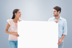Composite image of attractive young couple smiling and holding poster Royalty Free Stock Photography