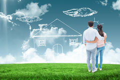 Composite image of attractive young couple standing with arms around Stock Image