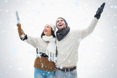 Composite image of attractive young couple in warm clothes with arms up Royalty Free Stock Photo