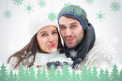 Composite image of attractive young couple in warm clothes blowing Stock Photo