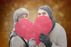 Composite image of attractive young couple in warm clothes holding red heart Stock Photos