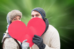 Composite image of attractive young couple in warm clothes holding red heart Stock Photography