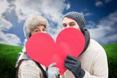 Composite image of attractive young couple in warm clothes holding red heart Royalty Free Stock Photography
