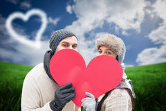 Composite image of attractive young couple in warm clothes holding red heart Stock Image