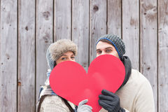 Composite image of attractive young couple in warm clothes holding red heart Royalty Free Stock Images