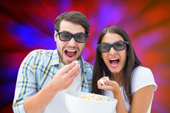 Composite image of attractive young couple watching a 3d movie Stock Photo