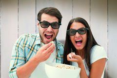 Composite image of attractive young couple watching a 3d movie Royalty Free Stock Images